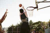 Man playing basketball with friends in court against clear sky 11100064612| 写真素材・ストックフォト・画像・イラスト素材|アマナイメージズ