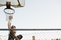 Low angle view of friends playing basketball against clear sky 11100064616| 写真素材・ストックフォト・画像・イラスト素材|アマナイメージズ
