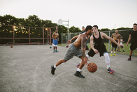 Male friends playing basketball on court against clear sky 11100064623| 写真素材・ストックフォト・画像・イラスト素材|アマナイメージズ