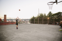 Friends practicing basketball on court against clear sky 11100064624| 写真素材・ストックフォト・画像・イラスト素材|アマナイメージズ