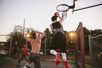 Male friends playing basketball in court during sunset 11100064625| 写真素材・ストックフォト・画像・イラスト素材|アマナイメージズ