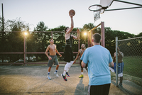 Friends looking at man dunking while practicing basketball in court during sunset 11100064626| 写真素材・ストックフォト・画像・イラスト素材|アマナイメージズ