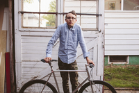 Portrait of man with bicycle standing against door at garage