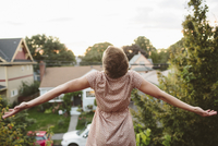 Rear view of happy woman with arms outstretched standing on rooftop against sky 11100064638| 写真素材・ストックフォト・画像・イラスト素材|アマナイメージズ