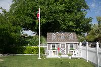 Playhouse by flag on grassy field at yard 11100067500| 写真素材・ストックフォト・画像・イラスト素材|アマナイメージズ