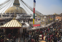 People walking round base of stupa during Lhosar, the Tibetan and Sherpa New Year festival, Bodhnath Buddhist Stupa, Bagmati, Ka