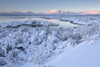 View towards Pingvallavatn Lake on a clear winter's afternoon with the shore and distant mountains covered in snow, Pingvellir N