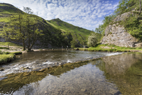 Dovedale reflections, hikers on stepping stones and Thorpe Cloud, limestone gorge in spring, Peak District, Derbyshire