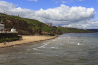Bathers on West Cliff Beach, backed by grassy cliffs in summer, Whitby, North Yorkshire