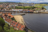 Tate Hill Beach, red roofed houses, town on West Cliff with backdrop of green hills in summer, Whitby, North Yorkshire