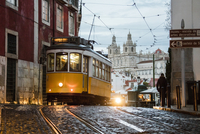 Romantic atmosphere in the old streets of Alfama with the castle in the background and tram number 28, Lisbon