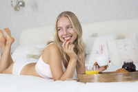 Young woman eating breakfast in bed. 11107000077| 写真素材・ストックフォト・画像・イラスト素材|アマナイメージズ