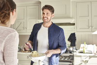 Mid adult married couple cooking together.