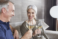 Mature married couple toasting with white wine.