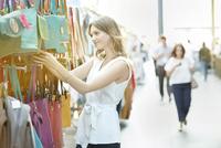 Young woman shopping for handbag at street market. 11107000313| 写真素材・ストックフォト・画像・イラスト素材|アマナイメージズ