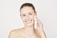 Teenage girl wiping face with cotton pad.