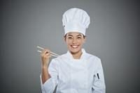 Portrait of young chef holding chopsticks.