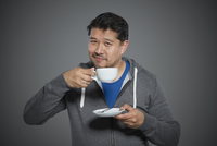 Portrait of mid adult man with tea cup and saucer.