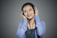 Portrait of mid adult woman listening to music on headphones.