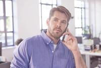 Mid adult businessman talking on smart phone.