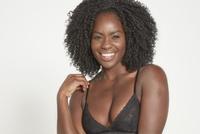 Smiling model wearing black bra.
