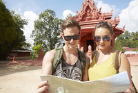 Young couple holding map by red temple
