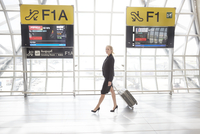 Young woman with suitcase walking in airport 11107001144| 写真素材・ストックフォト・画像・イラスト素材|アマナイメージズ