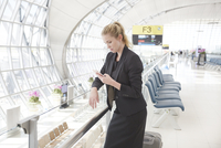 Young woman on mobile phone in airport departure area
