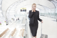 Young woman on mobile phone in airport 11107001165| 写真素材・ストックフォト・画像・イラスト素材|アマナイメージズ