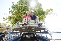 Young couple sitting on tour bus roof