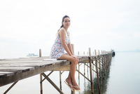 Young woman wearing floral dress sitting on pier