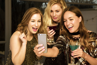 Young women taking selfie at party