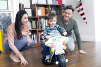 Boy on miniature motorcycle with parents