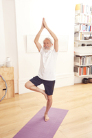 Senior man doing yoga on exercise mat