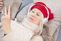 Senior woman using digital tablet and headphones 11107002382| 写真素材・ストックフォト・画像・イラスト素材|アマナイメージズ
