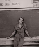 Portrait of woman leaning on blackboard