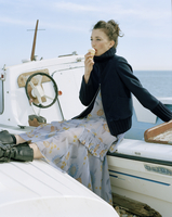 Young woman eating ice cream on boat