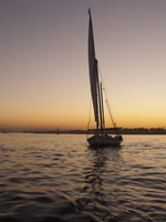 Sailing boat on water during sunset