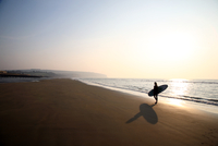 Silhouette of woman with surfboard on beach