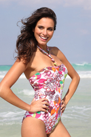 Young woman at beach in floral one piece swimsuit