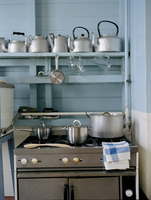 Stove in domestic kitchen with shelf of tea kettles