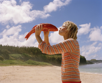 Young woman kissing red fish on beach