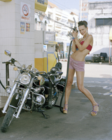 Young woman at petrol station with motorcycle