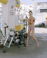 Young woman at petrol station with motorcycle 11107003760| 写真素材・ストックフォト・画像・イラスト素材|アマナイメージズ