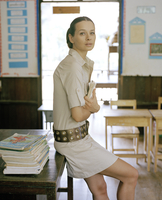 Young woman leaning on desk in classroom
