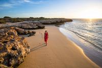 Osprey Bay, Cape Range National Park, Exmouth, Western Australia, Australia. Woman with elegant red dress and straw hat admiring 11108000241| 写真素材・ストックフォト・画像・イラスト素材|アマナイメージズ