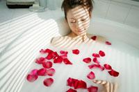 バラの花弁を浮かべた湯船に浸かる女性