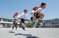 グラウンドで長縄跳びをする少年少女