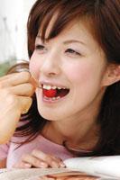 さくらんぼを食べる女性