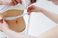 ウエストのサイズを測る女性